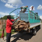 Joe works with the build team to unload coop wood and tin in Soroti.